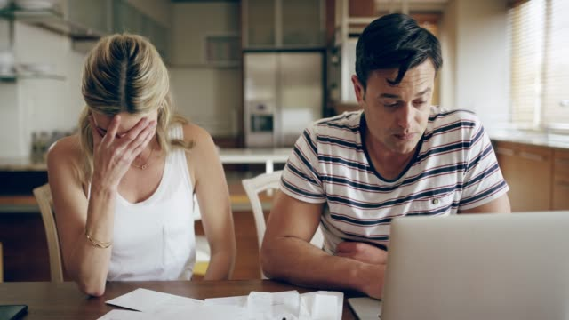 4k footage of a couple looking unhappy while doing their budget at home